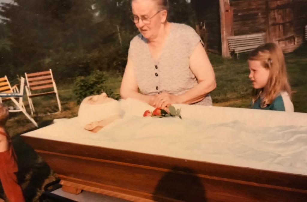 Vanha nainen ja nuori tyttö katsovat arkussa makaavaa kuollutta miestä.
