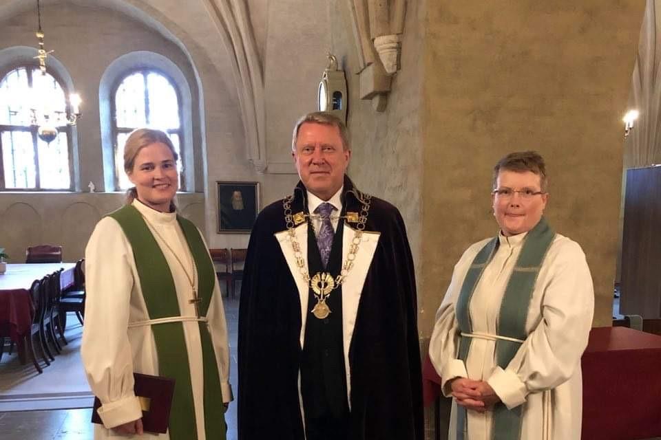 Piispa, rehtori ja yliopistopappi seisovat tuomiokirkon sakastissa.